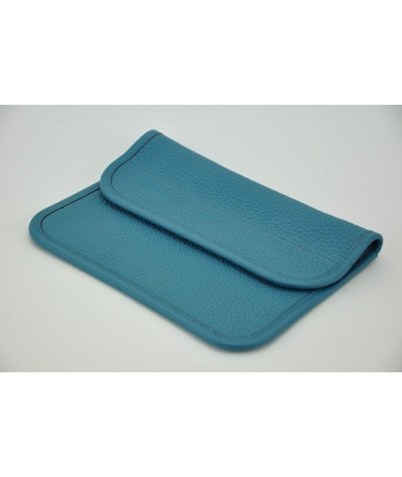 Pochette en taurillon bleu jean. Se ferme avec deux tops magnétiques.