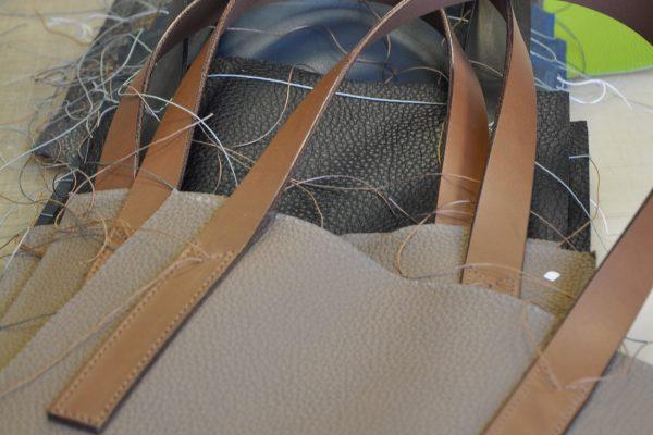 Les poignées sont montées en premier sur la face du sac en cuir. Fabrication LE NOËN maroquiniers du luxe en France.
