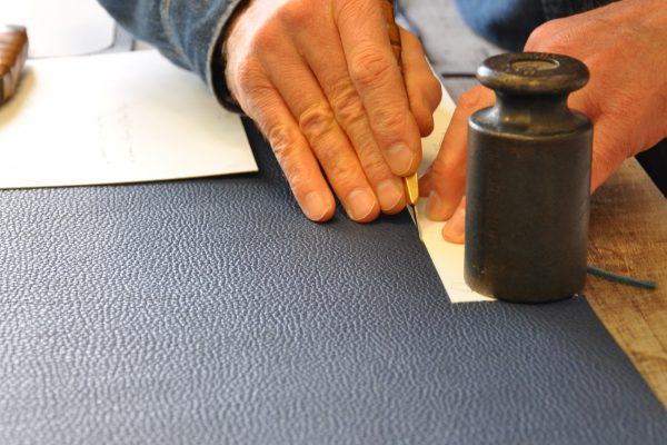 """La coupe du cuir se fait avec un couteau à pied où ici avec """"L'indispensable"""", précision et rigueur sont exigées. LE NOËN artisan maroquinier en France."""