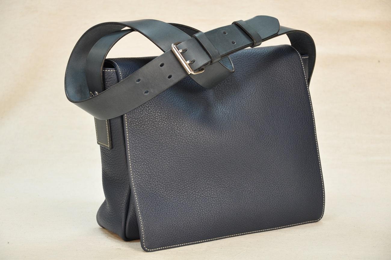 La besace Heidi est en taurillon bleu doublée en tissu Jean-Paul Gaultier. Fabrication française par maroquiniers du luxe.