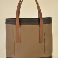 Sac pour femme en taurillon, association de la couleur taupe et marron, coutures marron clair. Création et fabrication LE NOËN France.