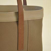 Le sac Valentine en cuir de taurillon a été imaginé avec deux poignées plates en vachette marron à tannage végétal. Se porte au bras ou à la main. Design et fabrication de la marque LE NOËN maroquiniers du luxe en Provence, France.