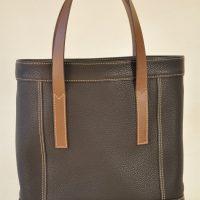 Le sac pour femme Valentine est en taurillon marron, doublé en lin, avec des poignées en vachette. Cette création est une exclusivité LE NOËN maroquiniers du luxe français.