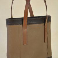 Le sac pour femme en taurillon a été imaginé avec des empiècements qui sont soulignés d'une double couture en fil marron clair. fabrication LE NOËN Maroquiniers du luxe en Provence.