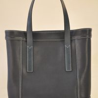 Le sac Valentine pour femme en vachette bleu lisse, se ferme avec deux boutons pressions cachés. Création et fabrication française par LE NOËN selliers maroquiniers.
