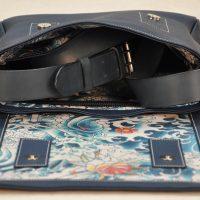 La besace pour femme et pour homme est en taurillon bleu, doublé en tissu lin/coton Jean-Paul Gaultier. Création et fabrication française. LE NOËN sellier maroquinier du luxe.